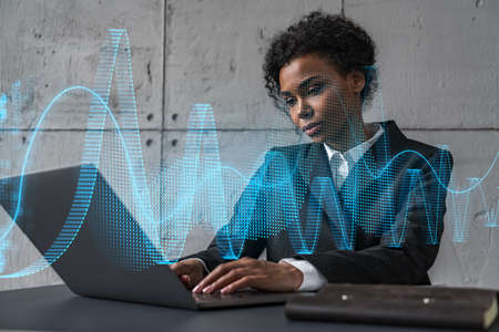 Businesswoman typing on laptop work in modern office on new project. financial market graph drawing hologram. Double exposure. Concept of success.