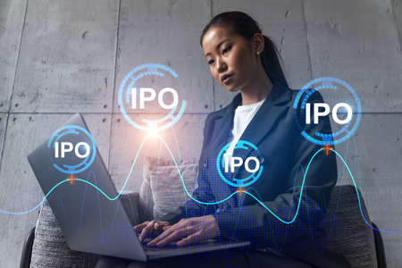 Businesswoman typing on laptop work in modern office on new project. IPO icon drawing hologram. Double exposure. Concept of success. Stock Photo