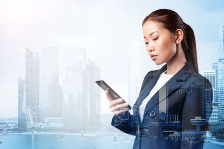 Prosperous astonishing young Asian business woman in suit texting phone the details of corporate meeting. Singapore cityscape. The concept of business communication. Double exposure.