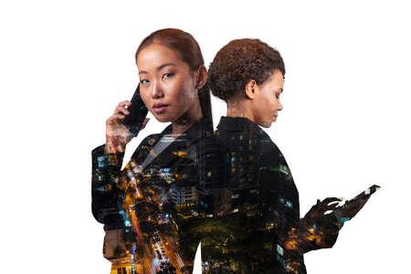 Double exposure of two young, successful, business people, woman, standing in front of Asian city Bangkok background. Concept of teamwork. Night time.