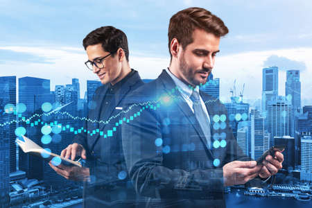 Two young handsome businessman in suits working on forecasting trading corporate strategy at fund. Forex chart. Singapore on background. Double exposure.