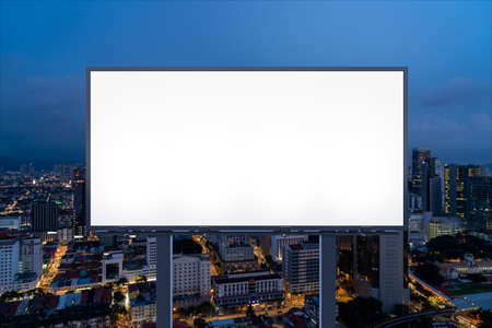 Blank white road billboard with KL cityscape background at night time. Street advertising poster, mock up, 3D rendering. Front view. The concept of marketing communication to promote or sell idea.