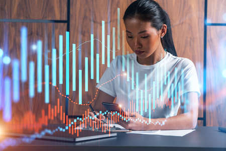 Woman takes notes with phone. Forex graph and chart online trade concept hologram. Multiexposure.