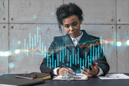Businesswoman taking notes and forex graph hologram. Double exposure. Business technology online trading stock market solution concept.