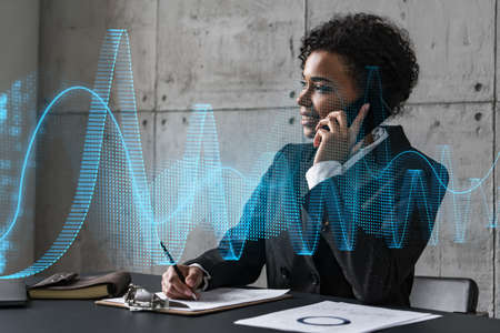 Businesswoman speaks phone and stock market financial graph hologram. Double exposure. Company statistics study concept. Stock fotó