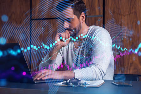 A serious caucasian analyst in casual wears, using laptop to proceed the forecast of stock market behavior. Double exposure. Forex Hologram. Concept of internet trading.