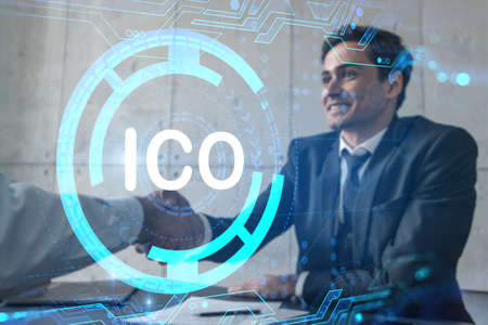 Two businessman shaking hands and ico icon hologram. Double exposure. Concept of initial coin offering. Handshake.