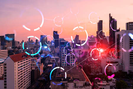Hologram of abstract technology glowing icons, panoramic cityscape of Bangkok at sunset, Asia. The concept of worlds technological changes. Double exposure.