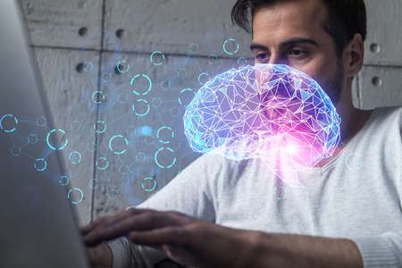 A serious caucasian man in casual wears, typing laptop to create a new artificial intelligence app. Double exposure. Hologram of a Brain.