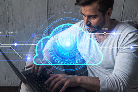 A serious caucasian man in casual wears, typing laptop to create a protection software to store confidential information. Double exposure. Hologram of an IT cloud. 版權商用圖片