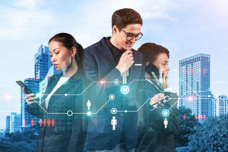Group of SMM specialists working on social media marketing strategy to achieve business goals. Hologram icons over Bangkok background.