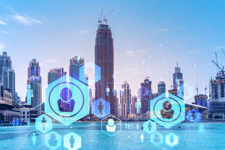 Skyscrapers of Dubai business downtown. International hub of trading and financial services. Social network icons hologram, concept of people connection. Double exposure. Dubai Canal waterfront.