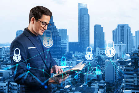 A young handsome eastern cybersecurity developer explores his notes from day planner to protect clients confidential information. IT lock icons over Bangkok city background.