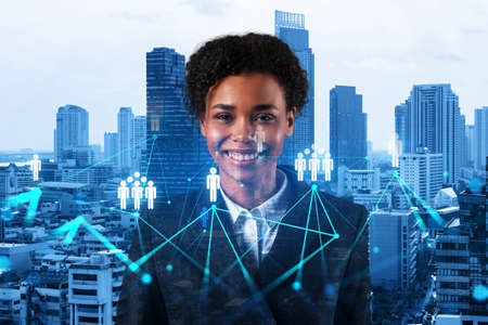 Smiling black woman HR director at international company is thinking about recruitment of highly qualified specialists. Women in business concept. Social media hologram icons over Bangkok.