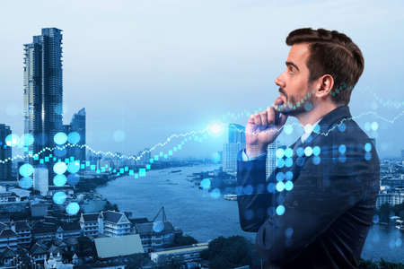 A young Caucasian handsome trader and stock market analyst in suit dreaming about market behavior and forecast in crisis. Trading at corporate finance fund. Forex chart. Bangkok. Double exposure