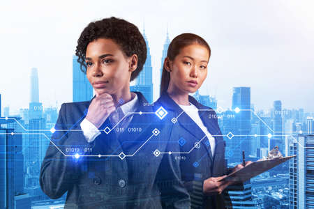 Two young astonishing businesswoman pondering about technology as a business necessity for tremendous growth in commerce. Tech hologram icons over Kuala Lumpur background.