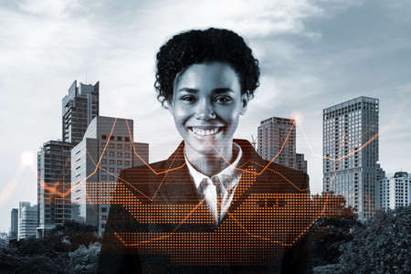 Successful smiling attractive black businesswoman in suit offering better conditions to investment banks clients. Woman in business concept. Financial charts hologram, Bangkok background. Banque d'images