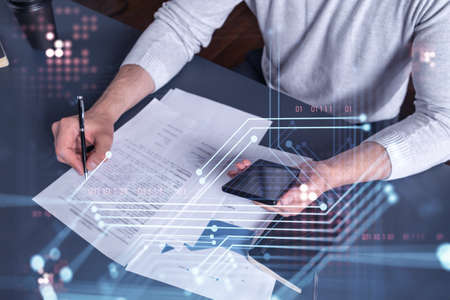 A client is signing the contract to create a software to present it at start up conference and gain investments for innovative service. Checking the details at smartphone. Hologram tech graphs.