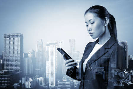 Prosperous astonishing young Asian business woman in suit texting phone the details of corporate meeting. Bangkok cityscape. The concept of business communication. Double exposure.