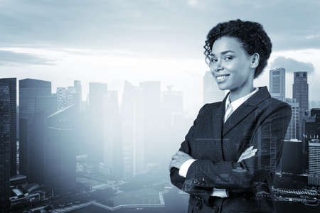 Smiling black African American business woman in suit in crossed arms pose. Singapore cityscape. The concept of woman in business. Investment fund. Double exposure.