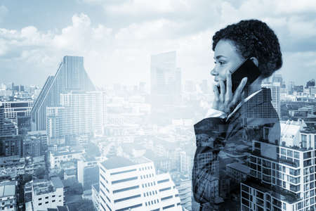 Successful smiling black African American business woman in suit pensively talking phone, Bangkok cityscape. The concept of consultants as problem solvers. Double exposure. Foto de archivo
