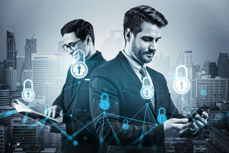 Two handsome businessman in suits working on project to protect clients confidential information at cybersecurity compliance division. IT lock icons over Bangkok background. Banque d'images