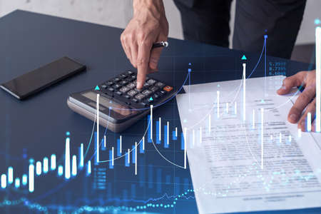 A trader computing historic data to predict stock market behavior. Internet trading concept. Forex and financial hologram chart over the desk and calculator.