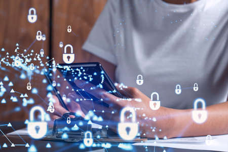 A businesswoman in casual wear signing the contract to prevent probability of risks in cyber security. Checking the phone. Padlock Hologram icons over the working desk. Women in business concept.