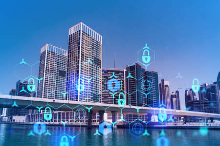 Skyscrapers of Dubai business downtown. International hub of trading and financial services. Lock icon hologram, concept of datum security. Double exposure. Dubai Canal waterfront.