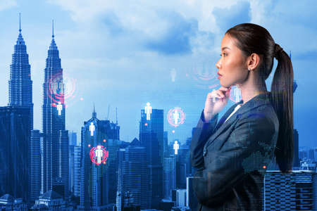 Attractive young Asian HR director at international company is thinking about recruitment of highly qualified specialists. Women in business concept. Social media hologram icons over Kuala Lumpur.