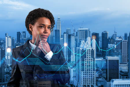 Attractive black businesswoman in suit pondering about new approaches to consultancy to find priorities for venture capital start up to estimate prospective growth. Financial chart on Kuala Lumpur.