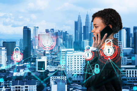 Attractive black businesswoman developer having conference call to protect clients confidential information by inventing solutions. IT lock icons over Kuala Lumpur city background.