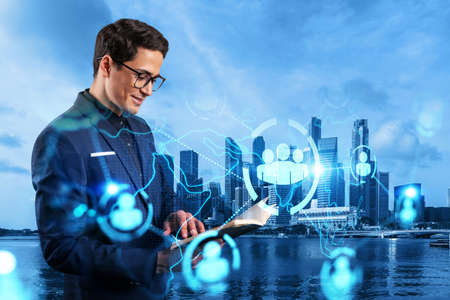 Handsome eastern HR director at international company is looking into personal organizer to plan business meeting to recruit highly qualified specialists. Social media hologram icons over Singapore. Stock fotó