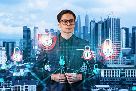 A young handsome eastern cybersecurity developer thinking about new concepts at security compliance division to protect clients confidential information. IT lock icons over Kuala Lumpur background. Stockfoto