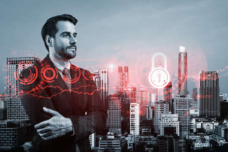 A young European cybersecurity developer in cross hand pose thinking about new concepts at security compliance division to protect clients information. IT lock icons over Bangkok background.