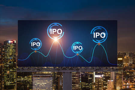 IPO icon hologram on road billboard over night panorama city view of Singapore. The hub of initial public offering in Southeast Asia. The concept of exceeding business opportunities.