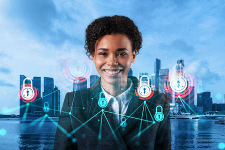 Successful smiling black businesswoman is thinking about new concepts at cybersecurity compliance division to protect clients confidential information. IT lock icons over Singapore background. Stockfoto