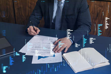 A client in formal wear is signing the contract to invest money in stock market. Internet trading and wealth management concept. Forex and financial hologram chart over the desk.