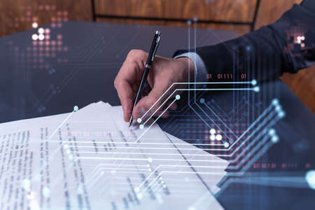 A client in dark blue suit is signing a contract to create a new software to present it in start up conference and gain investments to create a product. Technological graph over the desk.