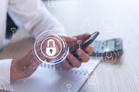 A programmer is browsing the Internet in smart phone to protect a cyber security from hacker attacks and save clients confidential data. Padlock Hologram icons over the typing hands. Formal wear. Stock Photo