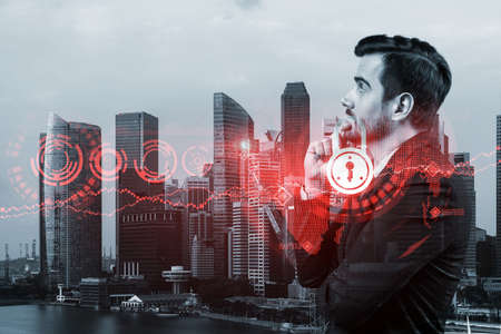 A young Caucasian cybersecurity developer thinking about new concepts at security compliance division to protect clients confidential information. IT lock icons over Singapore background.