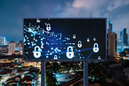 Padlock icon hologram on road billboard over panorama city view of Kuala Lumpur at night to protect business, Malaysia, Asia. The concept of information security shields.