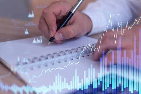 A trader in formal wear writing down some ideas to research stock market to proceed right investment solutions. Wealth management concept. Hologram Forex chart over close up shot. Banque d'images
