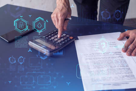 A research and development specialist computing the data to create a new approach to develop high tech business. Technological icons over the desk with calculator.