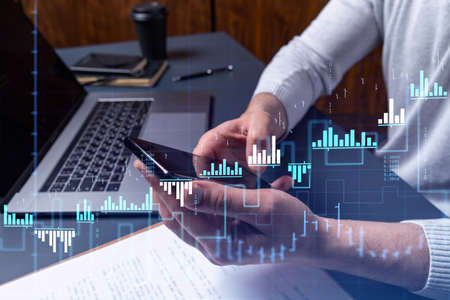 Trader holding in the hands a smart phone and researching stock market to proceed right investment solutions. Internet trading and wealth management concept. Hologram Forex chart over close up shot.