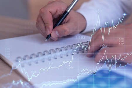 A trader in formal wear writing down some ideas to research stock market to proceed right investment solutions. Wealth management concept. Hologram Forex chart over close up shot.