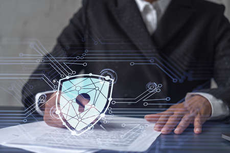 African American businesswoman in formal wear signing the contract to prevent probability of risks in cyber security. Padlock Hologram icons over the working desk. Women in business concept. Stock Photo