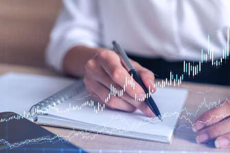 A woman trader in formal wear writing down some ideas to research stock market to proceed right investment solutions. Wealth management concept. Hologram Forex chart over close up shot.