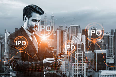 Caucasian successful analyst in suit checking the worldwide news using smartphone to set up effectively IPO to ensure the client new opportunities. Initial Public Offering. Kuala Lumpur