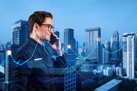 Handsome eastern analyst pensively processing conference call by phone to find financial solution for venture capital project. Hologram chart over Bangkok city background